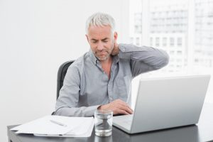 Man at desk with sore neck - Chiropractor physiotherapist